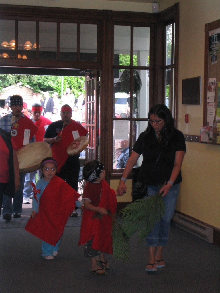 young Kwantlen members carrying cedar boughs to purify the spaceleading attendees in