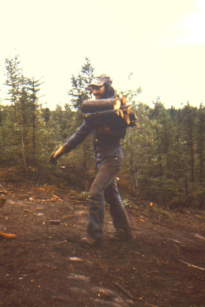 student excavator carrying wood for cooking fire