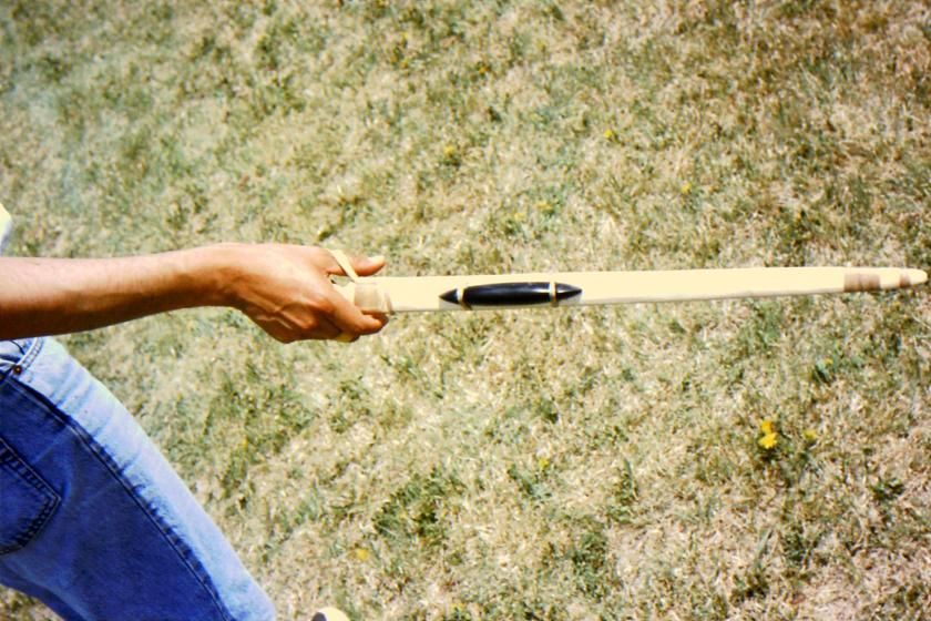 Young young participant demonstrating grip on atlatl throwing board.