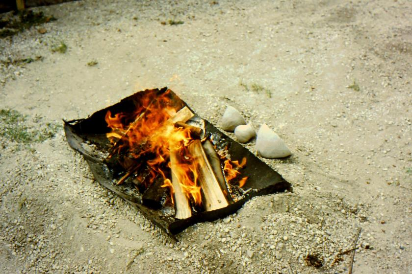 wet clay pots drying beside fire
